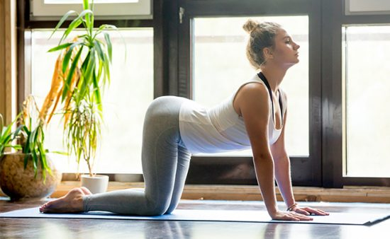 hard ab workout woman on floor arching back demonstrating pose