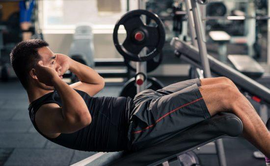 hard ab workout man on decline bench demonstrating decline curlup