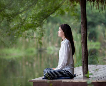 how to start your day woman meditating by water