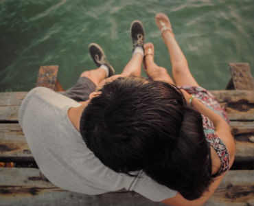 The law of attraction in relationships couple romantically sitting on dock