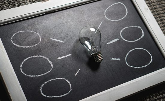 business operating at peak lightbulb on chalkboard