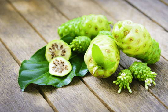 healing superfruits Noni fruit on wooden table