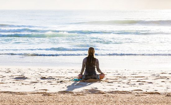 signs of depression woman sitting on sand looking at ocean