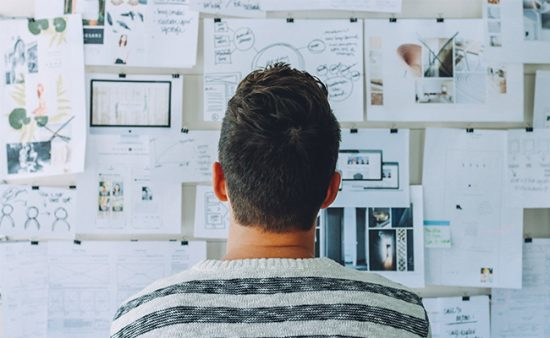 to do list man staring at wall of images