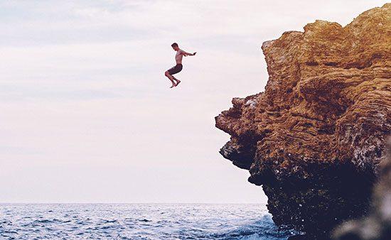 do i need a life coach man jumping off rocks into ocean