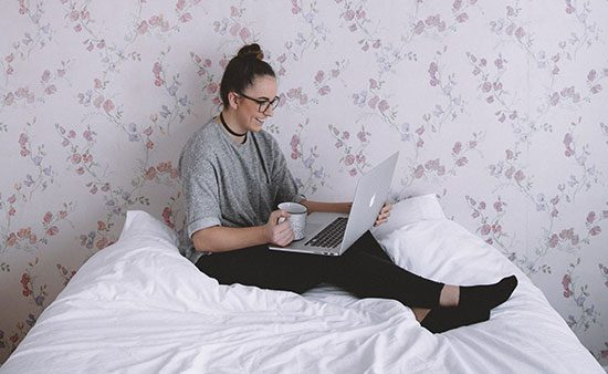 life management girl sitting on bed using laptop