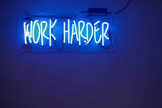 neon sign that says work harder