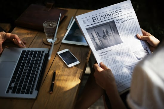 person reading the business section of the newspaper