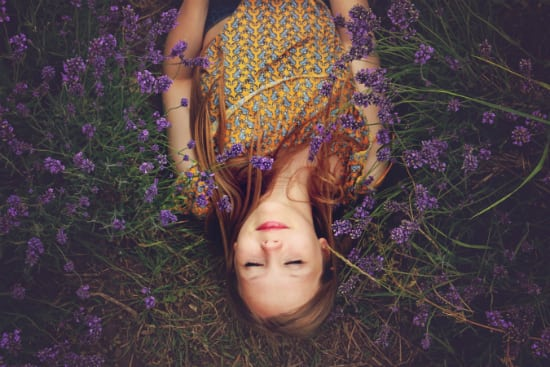girl laying peacefully in a field of flowers