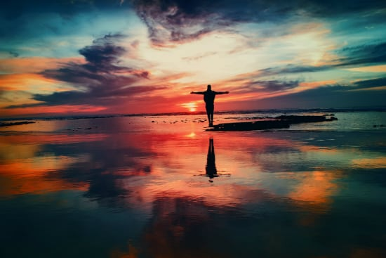 man standing in front of a beautiful sunset
