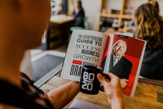a man is reading a book about the success and business growth